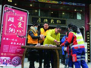 图为志愿者向群众发放腊八粥。樊荣 摄