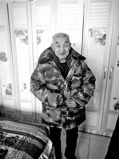 上图:吴洪甫高兴地穿上了军大衣。刘小龙摄