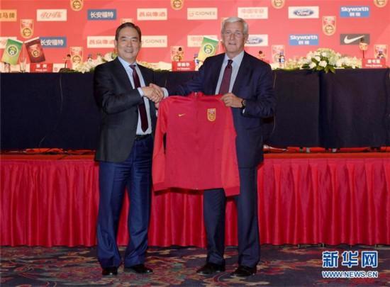 2016年10月28日,时任中国足协主席蔡振华(左)在媒体见面会上向国足新主帅里皮赠送国足球衣。 新华社记者郭勇摄