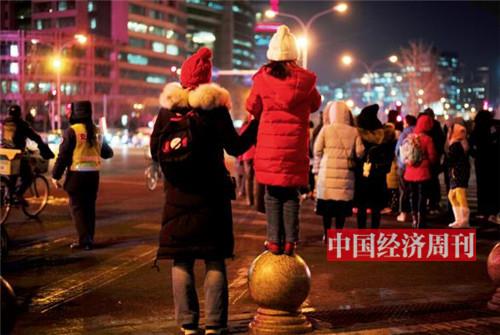 """P29-周末傍晚的海淀黄庄路口,""""黄庄妈妈""""带着孩子,穿梭在各式补习班。《中国经济周刊》首席摄影记者 肖翊  摄"""