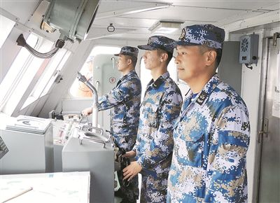 """上圖:官兵駕駛拖船行駛在""""十裡軍港""""。    段 鑫攝"""