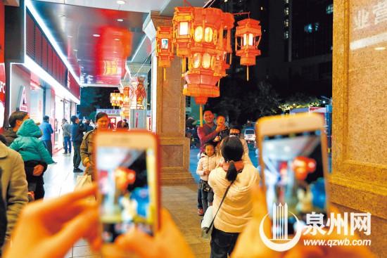 泉州商城广场上,一家子在灯下幸福合影。(林劲峰 摄)