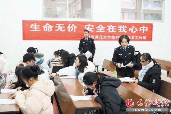 來自湖南警察學院的志願者正在為湖南師范大學來聽課的同學們發放宣傳單。  長沙晚報通訊員 歐陽志炫  攝