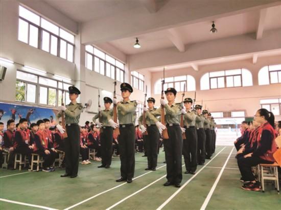 惠州市经济职业技术学院军鹰队给小学生进行升旗仪式端枪展示。