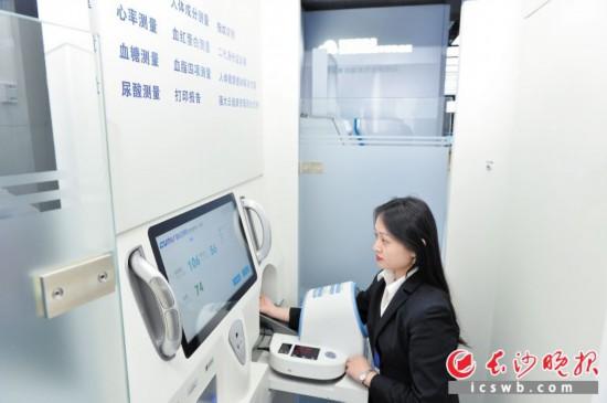 在透明计算智慧健康亭内可以完成14个大项和36个小项体检。图为工作人员正在体验。  长沙晚报全媒体记者 邹麟 摄
