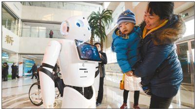 """近日,门诊导诊机器人""""小医""""在河北省邯郸市中心医院东区门诊大厅正式上岗,呆萌外表和有趣互动吸引不少患者围观。  郝群英摄"""