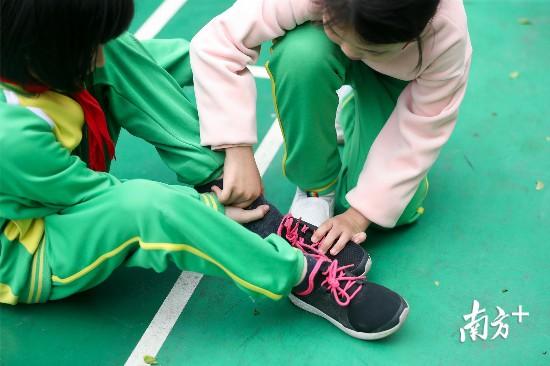 彤彤帮助潼潼穿鞋子。