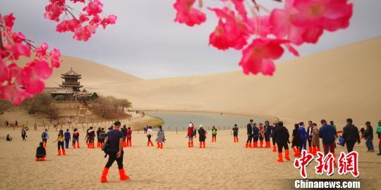 甘肃敦煌月牙泉畔柳绿花红游客酣畅春日沙海