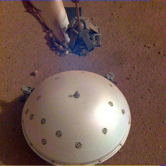 图为登录器上一个摄像头拍摄的照片,展示了火星车的圆形风热屏障,覆盖着内部结构地震实验装置,背景为火星表面。图片来源:NASA官网