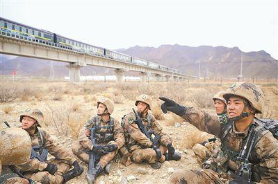 训练间隙,一辆火车沿青藏铁路驶过,周子杰(右一)为战友讲起自己一家和青藏线的不解之缘。薛子康 摄