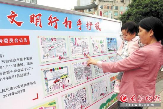 社区居民在雨花区砂子塘街道辖区学校孩子们创作的文明小报、漫画展板前驻足。长沙晚报通讯员 龙莉 摄