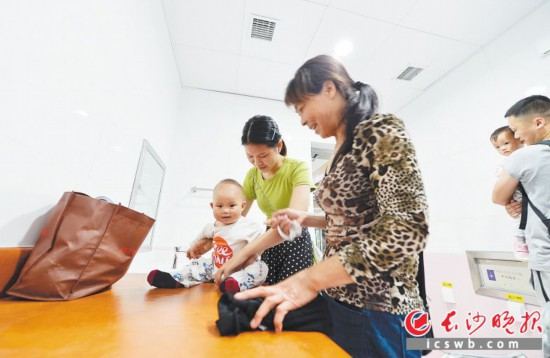 温馨服务   汉王陵公园站母婴室,尹女士正在给小孩换纸尿裤。地铁4号线一期工程每个站点都设有母婴室。均为长沙晚报全媒体记者 邹麟 摄