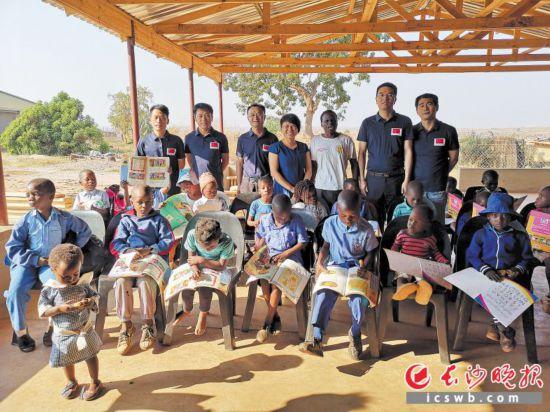 中国(快三官网app主页-南)第16批援津医疗队员为当地儿童义诊、送礼物,并与孩子们合影留念。援津医疗队供图