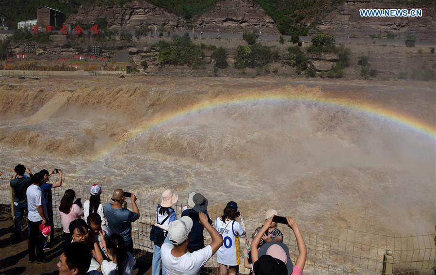 People watch scenery at Hukou Waterfall scenic spot in China's Shanxi