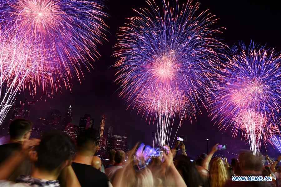People watch fireworks exploding during U.S. Independence Day celebration