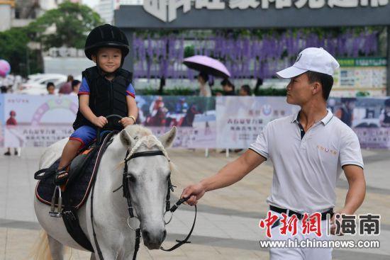 图为孩子现场体验骑马。