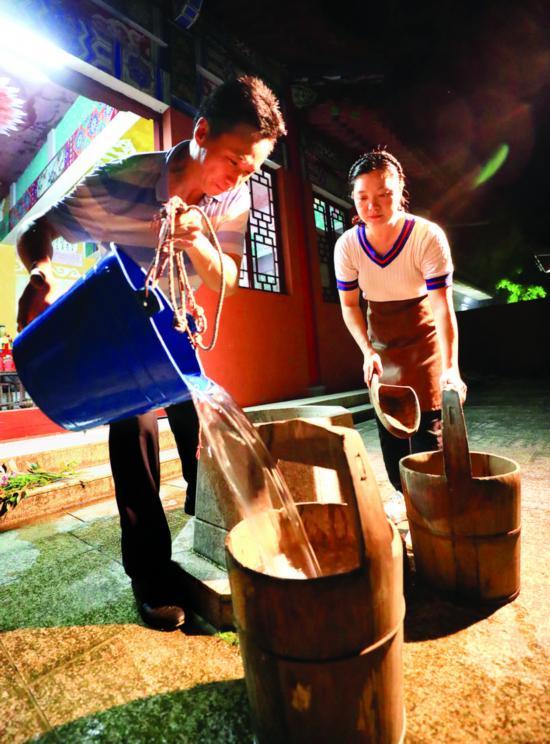 市民在罗浮山九天观古井中取七夕水。    惠州日报记者王建桥 摄