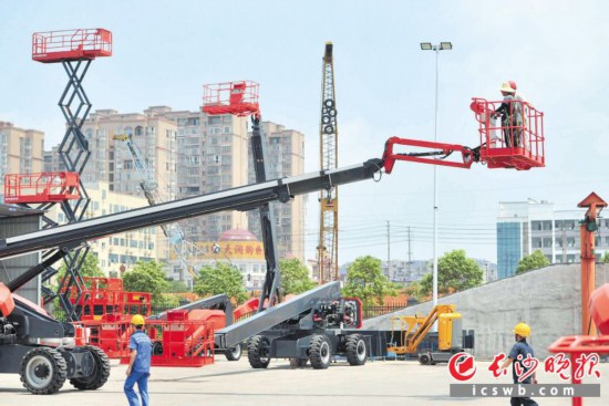 烈日下,一台台高空作业设备的立臂高高举起,技术人员站在平台上调试着产品。