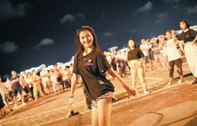 夜色下的海口湾街头表演 你是那颗最靓的星南渡江的出海口,有一个海口湾带状公园。人们在这里散步、约会、跳广场舞、玩轮滑、带着宠物聚会,它看起来似乎与别的公园广场没什么区别。但在今夏,海口湾突然在抖音平台上火了起来。