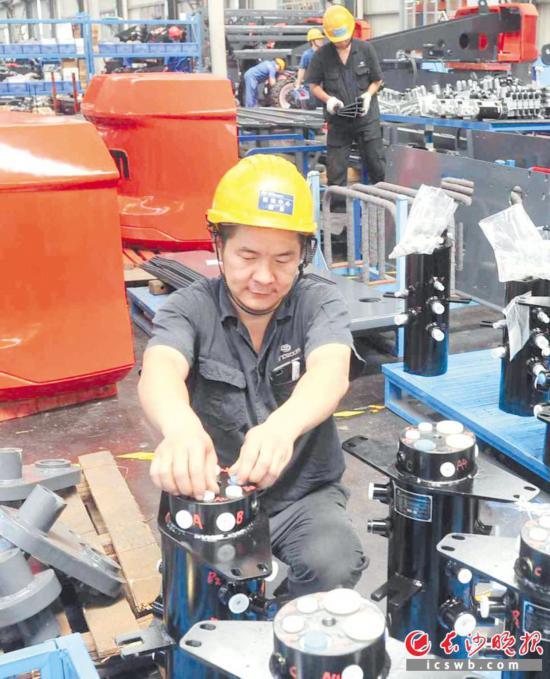 忙碌的工人们一个个汗湿衣背,有的在组装,有的在调试,生产场面火热。 均为长沙晚报全媒体记者 贺文兵 摄