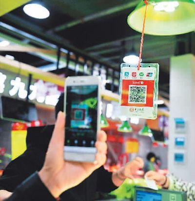 湖北省宜昌市のあるスマート農産物市場でQRコード決済で野菜を買う市民(撮影・張国栄)。