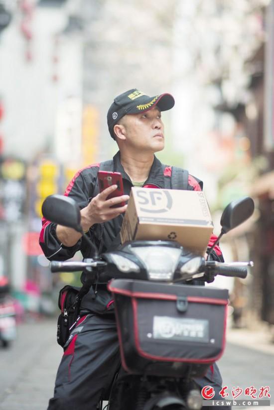 在长沙太平街,顺丰速运的一名快递员正在投递包裹。  长沙晚报全媒体记者 黄启晴 摄