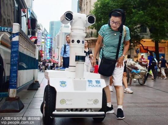 """9月9日,申城首位机器人""""警察""""在南京路步行街上岗巡逻,引来不少路人游客的好奇观看。"""