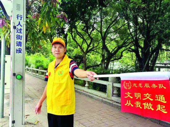 志願者在路口引導行人文明出行。    惠州日報記者馬海菊 攝