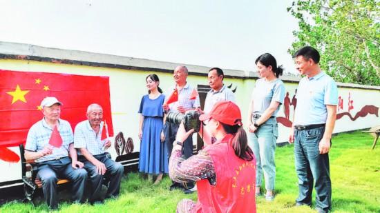 近日,长丰县吴山镇志愿者为镇敬老院的老人们拍摄与国旗合影照片,用特殊的方式献礼新中国成立70周年。   陶军 记者 宋炎骏 摄