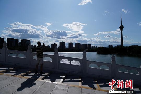北京の玉淵潭公園で、白い雲が浮かぶ青空の写真を撮る人(撮影・張興竜)。