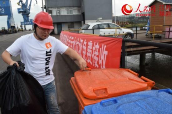 图为一船员将生活垃圾免费投入码头的垃圾桶内。