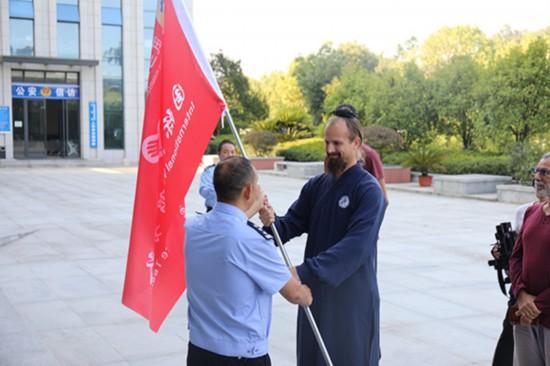 ボランティアチーム旗を受け取るジャックさん(画像・武当山公安局提供)。