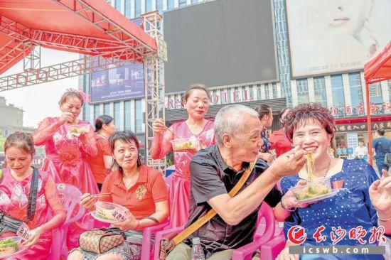 """一碗碱面,拌上芝麻酱、花生、榨菜,香喷喷地端到老人们手中。9月29日,在芙蓉区朝阳宇成广场,百位老人同食""""国庆面"""",为新中国庆生。  长沙晚报全媒体记者 周游 通讯员 彭裕田 摄影报道"""