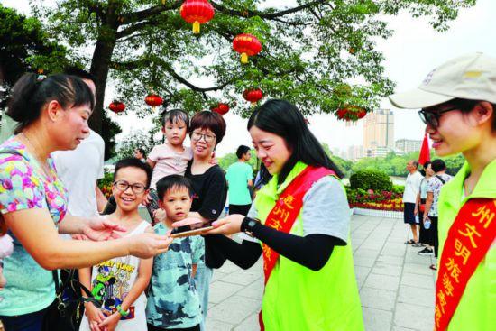 惠州文明旅游志愿者在西湖景区服务游人。  惠州日报记者钟畅新 摄