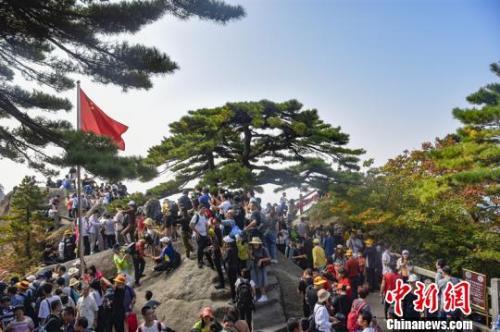 観光客でごった返す黄山の観光名所・迎客松(撮影・楊傳琳)。