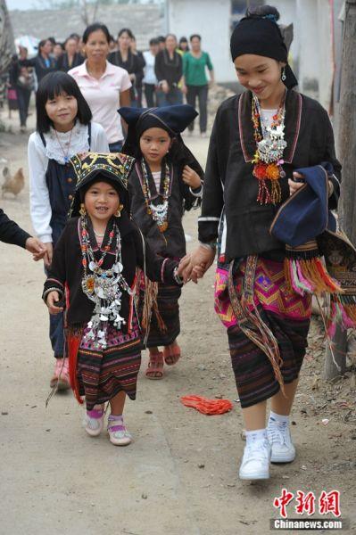 東方黎族美孚方言娃娃婚俗,四歲小新娘(中)在伴娘和親朋好友的陪同下走向新郎家。婚后新娘仍然居住在娘家。胡亞玲 攝