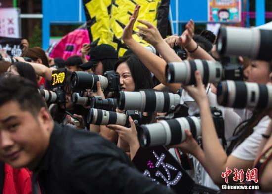 资料图:粉丝们在北京的一个粉丝嘉年华上架起长枪短炮拍摄偶像。<a target='_blank'  data-cke-saved-href='http://www.chinanews.com/' href='http://www.chinanews.com/'><p  align=