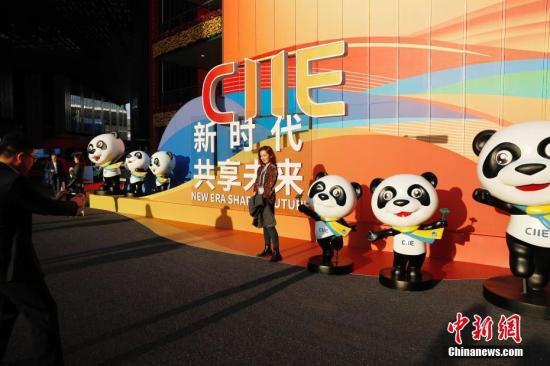 """资料图:11月5日,参观者与进博会吉祥物熊猫""""进宝""""合影留念。当日,第二届中国国际进口博览会在上海国家会展中心开幕。<a target='_blank'  data-cke-saved-href='http://www.chinanews.com/' href='http://www.chinanews.com/'><p  align="""