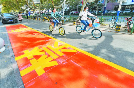 昨天,在合肥市第四十八中学门前,市民骑行经过禁停区。