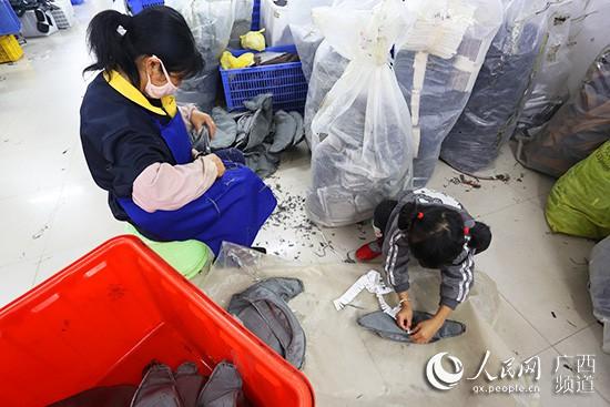 肖明燕的女儿帮助妈妈在皮具上贴标签 彭远贺/摄