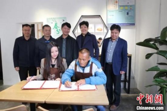 活动现场,台湾文创团队代表分别与茶油产业农人、农技站营运人员签订工作指导协议。 陈劲羽 摄
