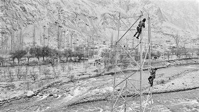电力工人在新疆深山的铁塔上安装