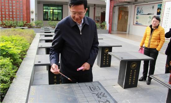 """1.何朝建在来宾市城南小学书法习作台上写下了""""民族团结""""的寄语_副本.jpg"""