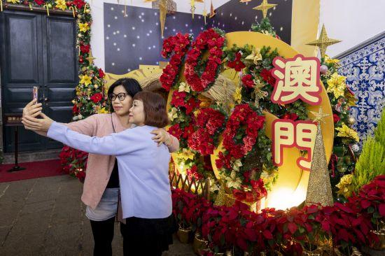 12月18日,民众在庆祝回归花坛前拍照留影。