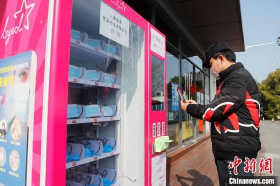マスクの自動販売機でマスクを購入する住民(撮影・殷立勤)。