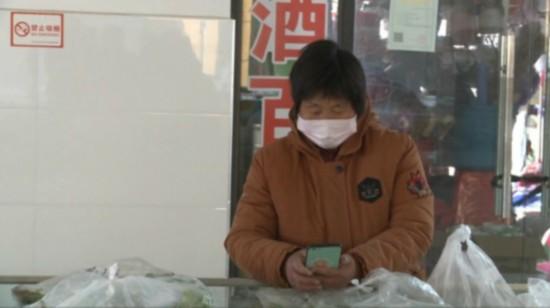 市民直接掃碼付錢拿菜 (劉登書 攝)