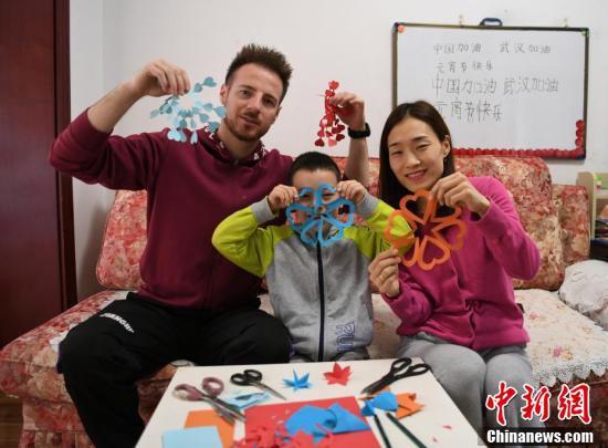 ネットを通じて切り紙細工について学ぶDaliさん一家(撮影・張瑶)。