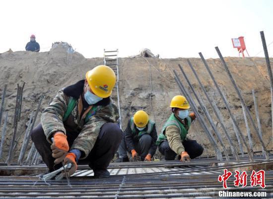 雄安新区K1快速道路(一期)プロジェクト第一セクションの施工現場でマスクをつけて作業にあたる作業員たち(2月11日撮影・韓氷)。
