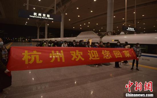 2月16日、「お帰りなさい、杭州へ」と書かれた横断幕を掲げて出稼ぎ労働者を出迎える企業社員(撮影・商澤陽)。