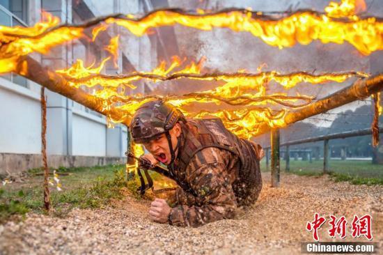 炎が燃え盛る障害物の下を素早くくぐり抜ける特殊部隊隊員(2月17日に撮影・余海洋)。
